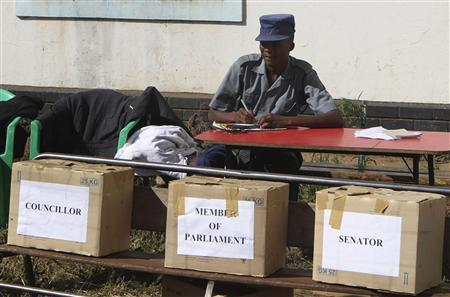 A policeman waits behind ballot boxes as supporters of President Robert Mugabe's ZANU PF party vote for candidates to stand in general elections expected later this year, in the capital Harare June 25, 2013. REUTERS/Philimon Bulawayo