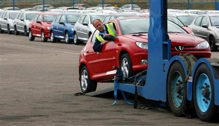 A worker loads a car onto a transporter at the PSA Peugeot Citroen Ryton plant in Coventry, central England, April 18, 2006. REUTERS/Darren Staples