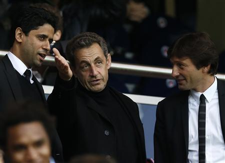 Former French President Nicolas Sarkozy (C) talks with Nasser Al-Khelaifi (L), Paris Saint Germain's club owner and owner of Qatari TV channel Al Jazeera Sport, President of beIN Sport French TV channel, and Paris Saint-Germain sports director Leonardo (R) as they attend the French Ligue 1 soccer match where Paris Saint-Germain faces Brest at the Parc des Princes stadium in Paris May 18, 2013. REUTERS/Gonzalo Fuentes