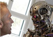 """Visitante olha para réplica do robô usado no filme """"O Exterminador do Futuro"""", na casa em que nasceu o ator Arnold Schwarzenneger, na vila de Thal, sul da Áustria. """"O Exterminador do Futuro"""" ganhará uma nova trilogia, disse o estúdio Paramount na quinta-feira. O primeiro filme da nova leva tem estreia prevista para junho de 2015. 7/10/2011. REUTERS/Herwig Prammer"""