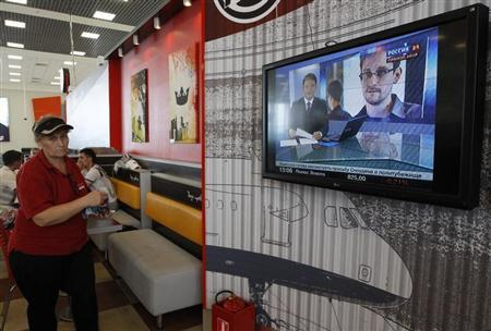 A television screens the image of former U.S. spy agency contractor Edward Snowden during a news bulletin at a cafe in Moscow's Sheremetyevo airport June 26, 2013. REUTERS/Sergei Karpukhin