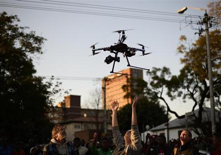 A journalist reaches up to catch a remote aerial camera that flew above crowds gathered outside the hospital where former South African President Nelson Mandela is being treated in Pretoria June 28, 2013. REUTERS/Dylan Martinez
