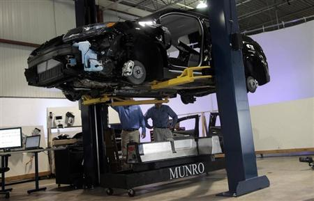 Team members raise a Chevrolet Volt electric vehicle on a hoist after releasing the battery from the underside at a design studio in Troy, Michigan January 18, 2012. REUTERS/Rebecca Cook