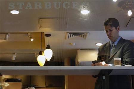 A man looks at his phone in a Starbucks store in New York June 25, 2013. REUTERS/Brendan McDermid