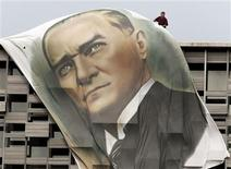 A worker fixes a giant portrait of Mustafa Kemal Ataturk at the top of the Ataturk Cultural Center in Istanbul's Taksim Square June 28, 2013. REUTERS/Osman Orsal