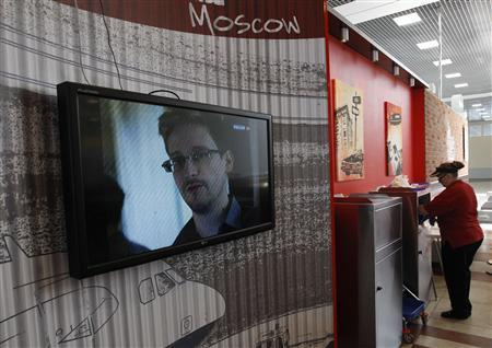 A television screens the image of former U.S. spy agency contractor Edward Snowden during a news bulletin at a cafe at Moscow's Sheremetyevo airport June 26, 2013. REUTERS/Sergei Karpukhin