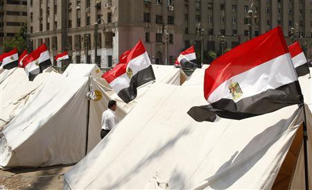 A protester walks among tents set up by protesters for their sit-in at Tahrir Square, ahead of the June 30 planned protest against President Mohamed Mursi, in Cairo June 29, 2013. REUTERS/Asmaa Waguih