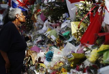 A woman looks at floral tributes, left for British soldier Lee Rigby, outside an army barracks near the scene of his killing in Woolwich, southeast London June 3, 2013. REUTERS/Luke MacGregor