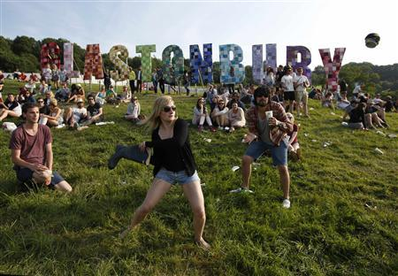 Festival goers play rounders with a wellington boot and a beer can on the first day of Glastonbury music festival at Worthy Farm in Somerset, June 26, 2013. REUTERS/Olivia Harris