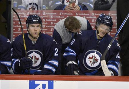 Winnipeg Jets' Tobias Enstrom (R) is attended to on the bench after being injured against the Buffalo Sabres during the first period of their NHL hockey game in Winnipeg April 9, 2013. REUTERS/Fred Greenslade