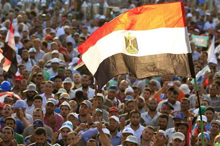 Members of the Muslim Brotherhood and supporters of Egyptian President Mohamed Mursi shout slogans and waves an Egyptian flag during a protest around the Raba El-Adwyia mosque square in Nasr City, in the suburb of Cairo June 29, 2013. REUTERS/Mohamed Abd El Ghany