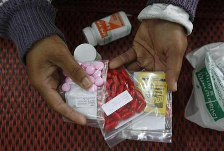 An HIV-infected patient displays medicine at a hospital in Payao province, about 600 km (373 miles) north of Bangkok November 28, 2007. REUTERS/Sukree Sukplang