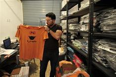 An employee holds up a t-shirt at the popular clothing store Boza in Benghazi June 26, 2013. REUTERS/Esam Al-Fetori