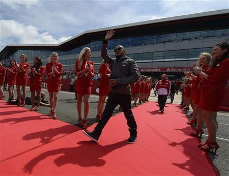 Mercedes Formula One driver Lewis Hamilton of Britain waves during the drivers parade ahead of the British Grand Prix at the Silverstone Race circuit, central England, June 30, 2013. REUTERS/Nigel Roddis