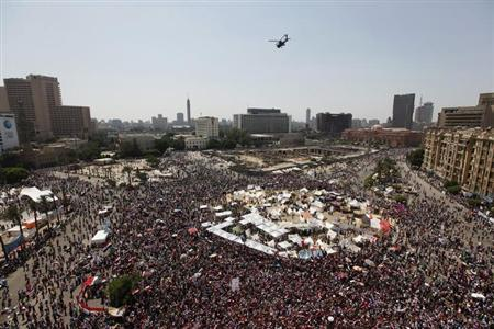 A military helicopter flies above Tahrir square as protesters opposing Egyptian President Mohamed Mursi demonstrate in Cairo June 30, 2013. REUTERS/Mohamed Abd El Ghany