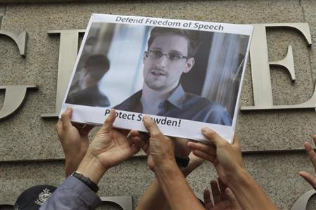 Protesters supporting Edward Snowden, a contractor at the National Security Agency (NSA), hold a photo of Snowden during a demonstration outside the U.S. Consulate in Hong Kong June 13, 2013. REUTERS/Bobby Yip