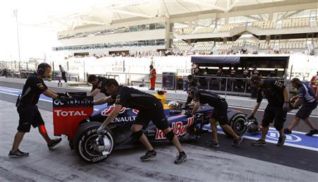 Crew members push the car of Red Bull Formula One driver Red Bull Formula One driver Sebastian Vettel of Germany during the first practice session of the Abu Dhabi F1 Grand Prix at the Yas Marina circuit on Yas Island November 2, 2012. REUTERS/Ahmed Jadallah