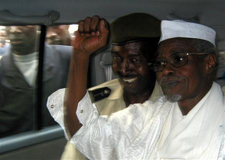 Former Chad President Hissene Habre (R) raises his fist in the air as he leaves a court in Dakar escorted by a Senegalese policeman November 25, 2005. REUTERS/Aliou Mbaye