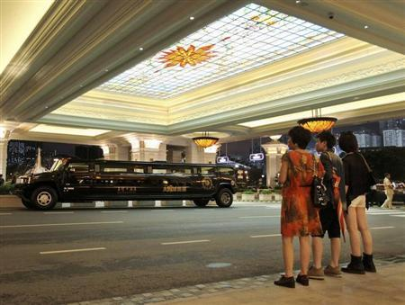 Visitors stand opposite a limousine featuring the company logo of Suncity Group outside Macau Galaxy resort in Macau June 23, 2013. REUTERS/Paul Yeung