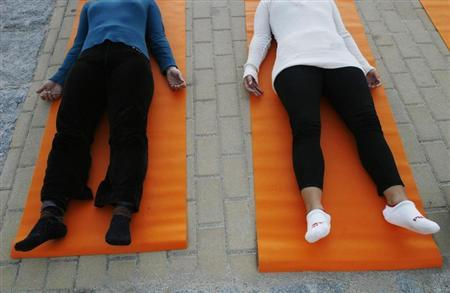 People take part in a free yoga class at the Parque del Oeste in Madrid September 27, 2007. REUTERS/Susana Vera