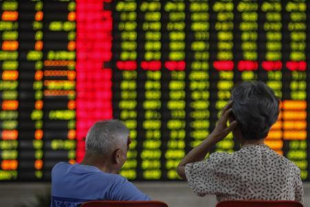 Investors sit in front of an electronic board showing stock information at a brokerage house in Shanghai June 25, 2013. REUTERS/Aly Song