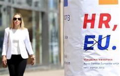 """Женщина проходит мимо объявления о вступлении Хорватии в ЕС, на котором кто-то зачеркнул слово """"ЕС"""", в Загребе 30 июня 2013 года. Хорватия стала в понедельник 28-м членом Европейского Союза, пройдя долгий путь от составной части социалистической Югославии и жестокой войны за независимость до демократического государства с рыночной экономикой. REUTERS/Antonio Bronic"""