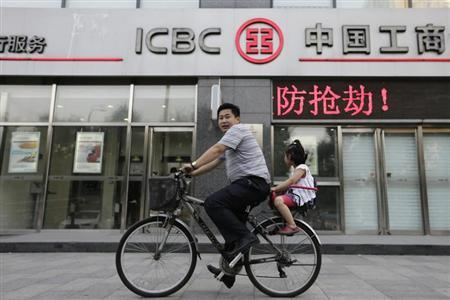 A man cycles a bike carrying his daughter past a branch of Industrial and Commercial Bank of China Ltd (ICBC) in Beijing, June 26, 2013. REUTERS/Jason Lee