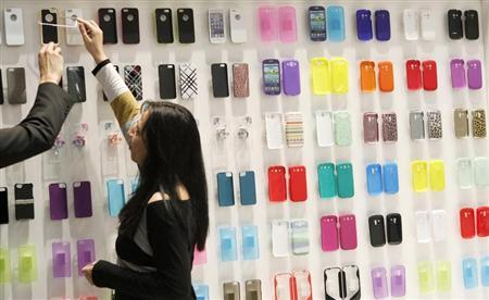 A visitor looks at mobile phone covers at the Mobile World Congress in Barcelona February 28, 2013. REUTERS/Albert Gea