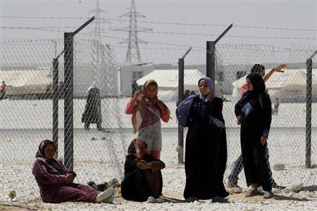 A group of Syrian refugees wait for a bus to return them to their homeland at the Al-Zaatri refugee camp in the Jordanian city of Mafraq, near the border with Syria June 25, 2013. REUTERS/Muhammad Hamed