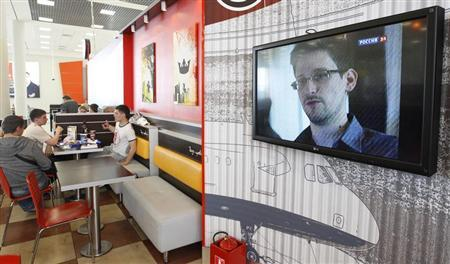 A television screen shows former U.S. spy agency contractor Edward Snowden during a news bulletin at a cafe at Moscow's Sheremetyevo airport June 26, 2013. REUTERS/Sergei Karpukhin
