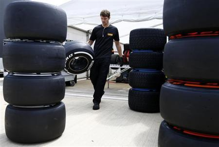 A Pirelli technician carries a tyre ahead of the British Grand Prix at the Silverstone Race circuit, central England, June 27, 2013. REUTERS/Darren Staples