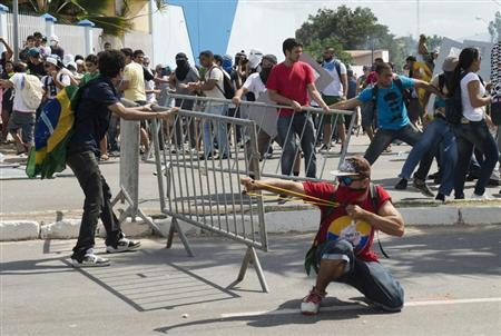 A demonstrator uses a slingshot to launch stones at policemen during protest near the Estadio Castelao, where the Confederations Cup semi-final match between Spain and Italy is being played, in Fortaleza June 27, 2013. REUTERS/Davi Pinheiro