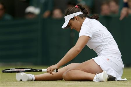 Laura Robson of Britain slips during her women's singles tennis match against Kaia Kanepi of Estonia at the Wimbledon Tennis Championships, in London July 1, 2013. REUTERS/Eddie Keogh