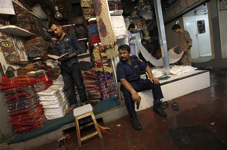 A private armed security guard keeps his eyes on a passage as shopkeepers work along a covered cloth market in Karachi June 13, 2013. REUTERS/Akhtar Soomro