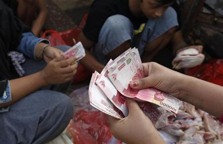 A vendor receives cash from her customer at a street market in Jakarta July 1, 2013. REUTERS/Enny Nuraheni