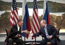 """Президент РФ Владимир Путин (справа) пожимает руку американскому коллеге Бараку Обаме на встрече в рамках саммита """"Большой восьмерки"""" в Северной Ирландии 17 июня 2013 года. Владимир Путин отказался высылать поселившегося в транзитной зоне московского аэропорта Шереметьево Эдварда Сноудена, который разоблачил американские спецслужбы, но согласился позволить ему жить в России в случае, если тот перестанет наносить вред США. REUTERS/Kevin Lamarque"""