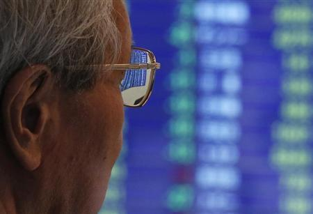 A man looks at an electric stock quotation board at a brokerage firm in Tokyo June 20, 2013. REUTERS/Issei Kato/Files