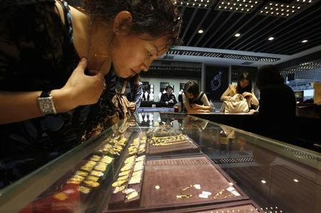 A customer looks at a few 24K gold keys left on an shelf inside a jewellery store at Hong Kong's Mongkok district April 23, 2013. REUTERS/Bobby Yip/Files