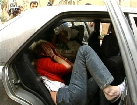 Samia Nakhoul, now Reuters Middle East Editor, is seen in the back of a car after being wounded at the Palestine Hotel in Baghdad, April 8, 2003, in this image taken from video footage. REUTERS/Pool via Reuters/Files