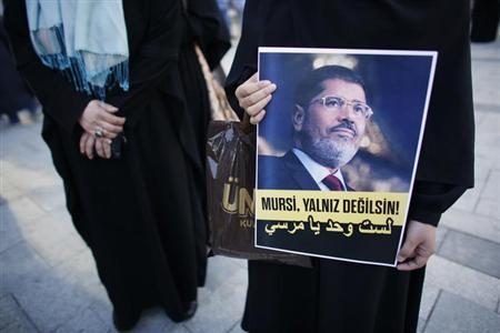 A woman holds a poster of Egypt's President Mohamed Mursi during a pro-Islamist demonstration in Istanbul July 1, 2013. The slogan on the poster reads, ''Mursi, you are not alone!'' REUTERS/Murad Sezer