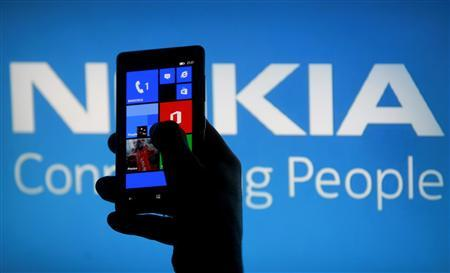 File photo of a woman posing with a Nokia Lumia smartphone in this photo illustration in the central Bosnian town of Zenica, May 6, 2013. REUTERS/Dado Ruvic/Files
