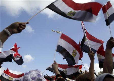 Anti-Mursi protesters wave with their flags happily to a military helicopter passes over where protesters chant slogans in a square where anti-Mursi protesters gather for the third day in Alexandria, July 2, 2013. REUTERS/Asmaa Waguih