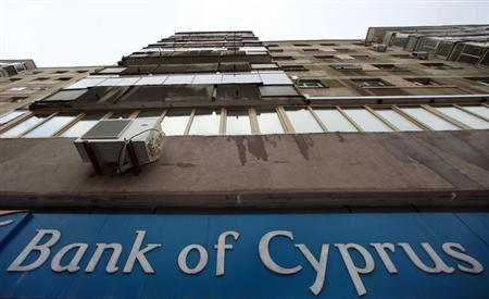 A Bank of Cyprus sign is seen on an apartment block in Bucharest March 28, 2013. REUTERS/Radu Sigheti