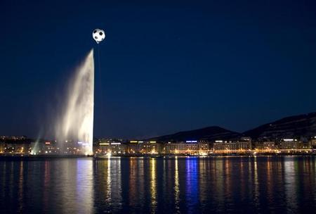 A giant helium-inflated soccer ball flies over the jet d'eau, or water fountain, at the Lac Leman in Geneva April 29, 2008. REUTERS/Valentin Flauraud/Files
