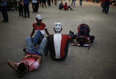 Protesters, wearing Guy Fawkes masks, who oppose Egyptian President Mohamed Mursi take part in a protest demanding that Mursi resign at Tahrir Square in Cairo July 2, 2013. REUTERS/Suhaib Salem