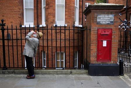 A man drinks from a can of Coke near a post box in London September 25, 2010. REUTERS/Kevin Coombs