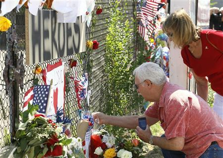 People look at mementos at a memorial dedicated to the 19 firefighters killed in the nearby wildfire in Prescott, Arizona July 2, 2013. REUTERS/Rick Wilking