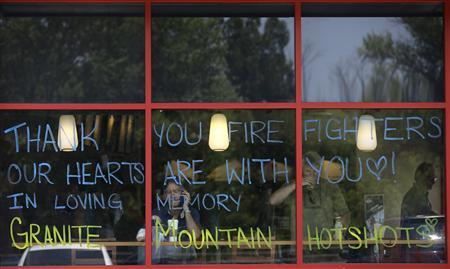 A tribute message for firefighters is displayed on the windows of a coffee shop in Prescott, Arizona July 1, 2013. REUTERS/Joshua Lott