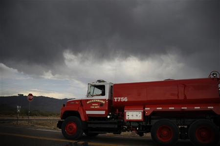A vehicle travels near monsoon storm cells passing over Yarnell area with rain that helped firefighters in Congress, Arizona July 1, 2013, a day after an elite squad of 19 Arizona firefighters were killed in the worst U.S. wildland fire tragedy in 80 years. REUTERS/Gene Blevins