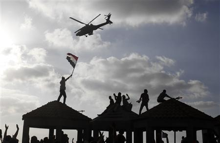 Supporters of President Mohamed Mursi wave to a military helicopter passing over them during a protest in Alexandria to counter anti-Mursi protests elsewhere in Alexandria, July 2, 2013. Mursi clung to office on Tuesday after rebuffing an army ultimatum to force a resolution to Egypt's political crisis, and the ruling Muslim Brotherhood sought to mass its supporters to defend him. REUTERS/Asmaa Waguih